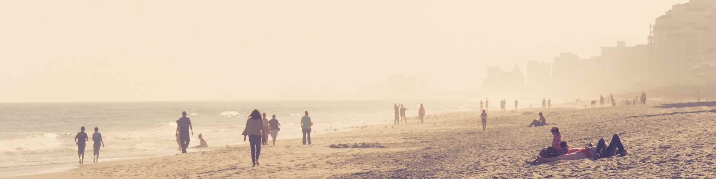 Hazy Silhouetted Scene Of People Walking And Sitting On The Beach At Myrtle Sc